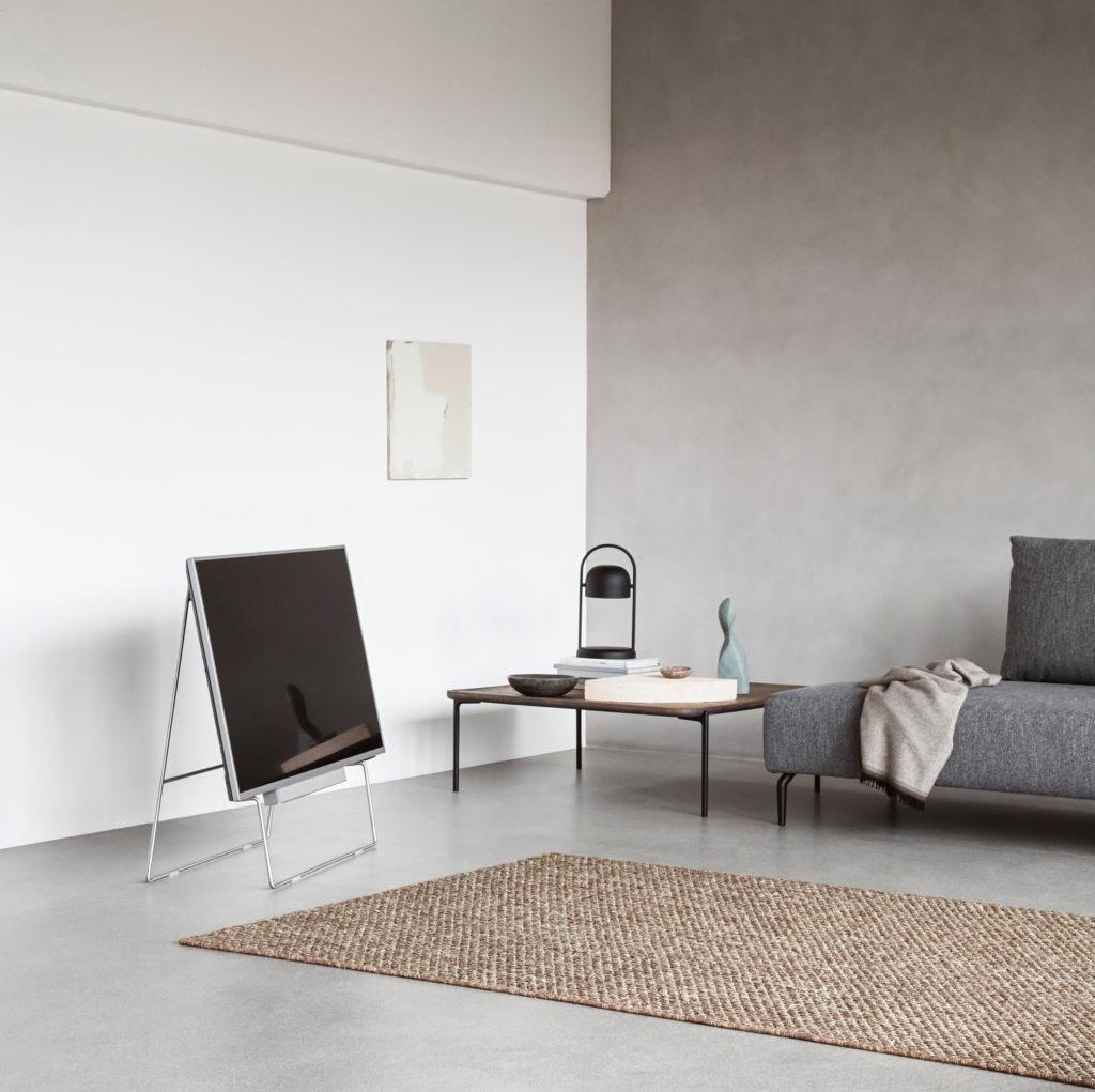 Det er ikke mere end et år siden Eva Solo lancerede en møbelkollektion og nu bevæger de sig ind i teknologiens verden med en minimalistisk og super smuk TV-stander. Den har fået navnet Carry, og kan give selv den mest klodsede fladskærm en skandinavisk lethed.